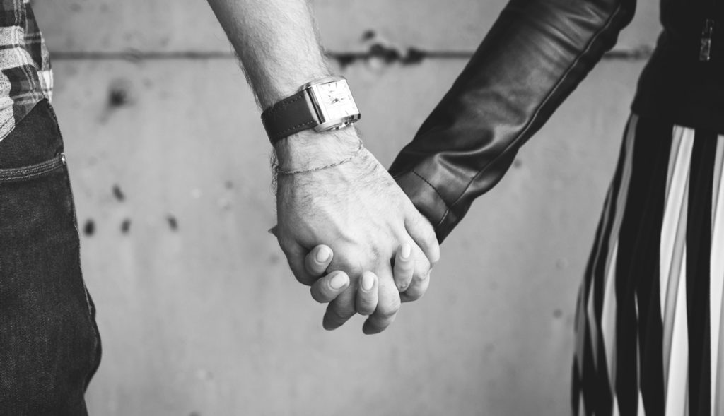 Black and white photo of a man and woman holding hands