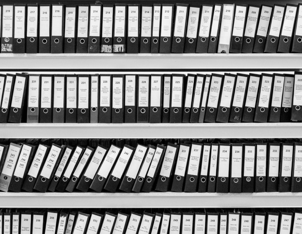 Black and white photo of reference books on shelves at a library