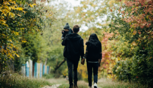 Photo of a young couple walking through the woods and holding hands in Fall. The man is holding a small child.
